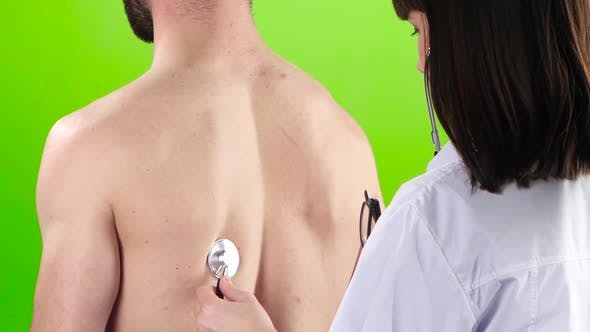Thumbnail for Woman Doctor Is Listening Lungs Man Stethoscope. Green Screen