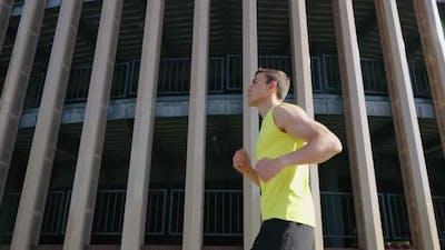 Athlete Jogging Against Building in Slow Motion