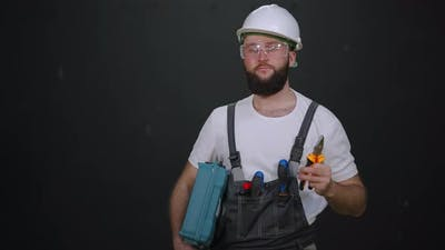 Skilled Cheerful Workman in Hard Hat and Overall with Tools