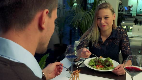 Thumbnail for A Man and Woman Sit at a Table in a Restaurant, Eat and Talk