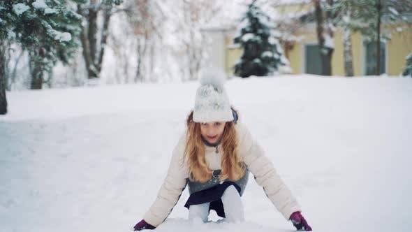 Kind zerstreut Schnee mit ihren Händen auf dem Hintergrund des Schneefalls im Park