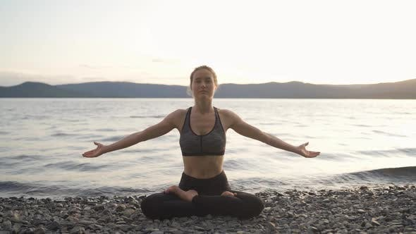 Young Attractive Girl Practices Yoga By the Lake at Sunset