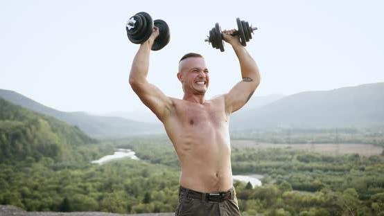 Thumbnail for Vorderansicht von gutaussehenden zielstrebig starken jungen Athlet mit nacktem Torso, der Kraftübungen macht