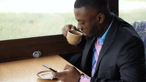 Afro American Businessman is Typing a Message on Smartphone Sitting in Cafe