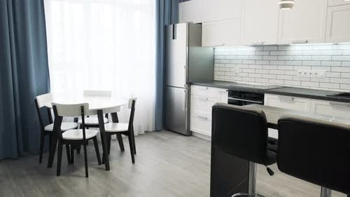 Steadycam Shows Elegant Modern Kitchen with White Walls. Light Interior of a White Kitchen in a