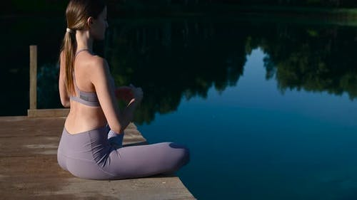 Girl Is Practicing Yoga Technique While Sitting on the Pier in Lotus Pose By the Lake and Meditating