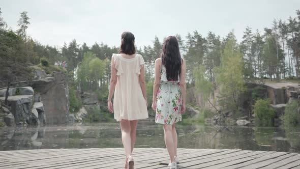 Thumbnail for Two Cute Young Women Wear Summer Dresses Standing in the Top of Rock and Looking at Amazing View