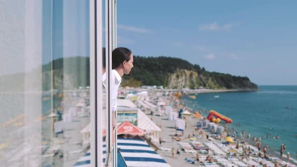 Young Woman in White Summer Dress Gazing at Beach at Sea From your Room Window