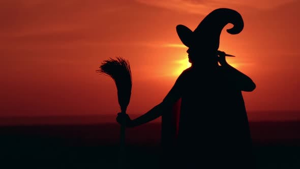 Thumbnail for Girl in Fancy Dress Witch Holds a Broom Looking on Sunrise