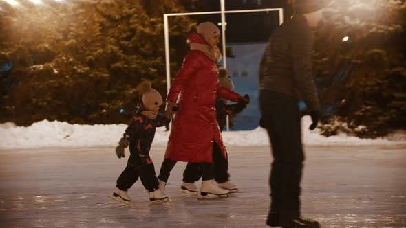 Thumbnail for A Family of Young Mother and Two Kids Skating on the Ice Rink Holding Their Hands
