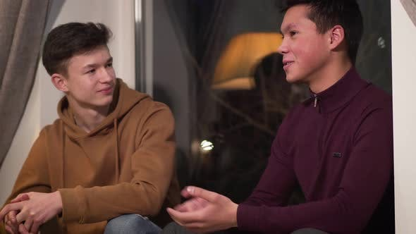 Thumbnail for Portrait of Caucasian and Asian Friends Talking and Giving Dap. Teenage Friends Spending Evening