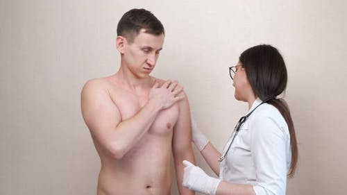 Woman Doctor in Gloves Examines Irritated Chest of Patient