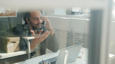 Middle Eastern Office Worker Talking on Mobile Phone and Smiling in Modern Glass Wall Office