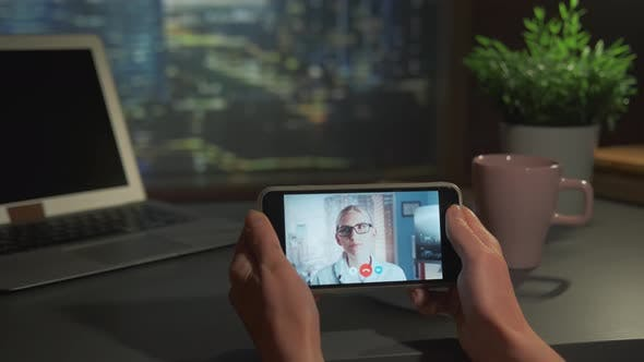 Woman Holding Smartphone with Video Calling to the Blonde Female Doctor in Glasses