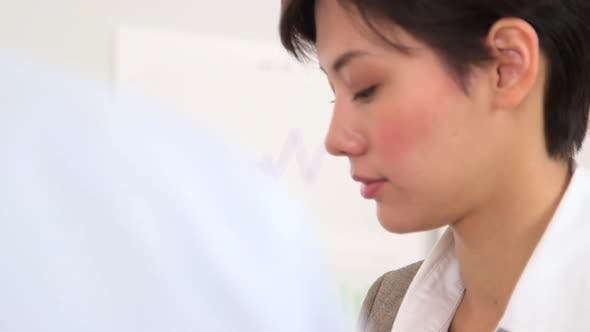 Thumbnail for Chinese businesswoman discussing company finances