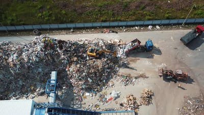 The excavator shovels up a bunch of garbage