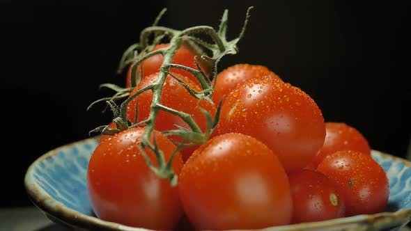 Thumbnail for Juicy ripe cherry tomatoes rotate on a dark background