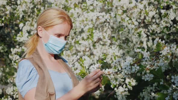 Cover Image for A Woman in a Gauze Bandage Examines a Flower Against a Blossoming Tree, Allergic Disease Problems
