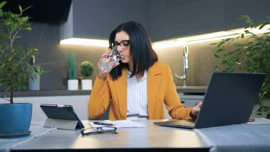 Woman in Glasses and Stylish Jacket Working with Documents and Laptop