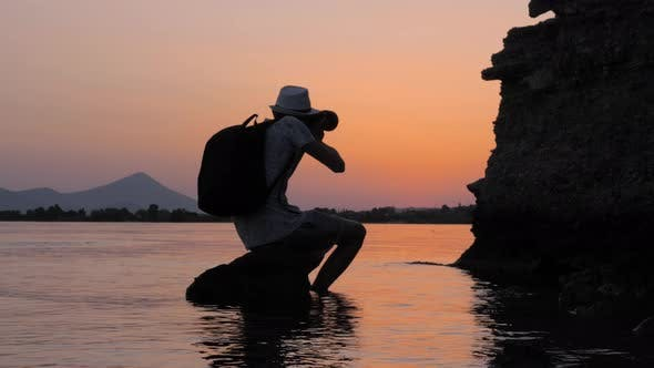Cover Image for Artist Taking Photo for Stocks. Young Male Photographer Taking Best Photo During Sunset
