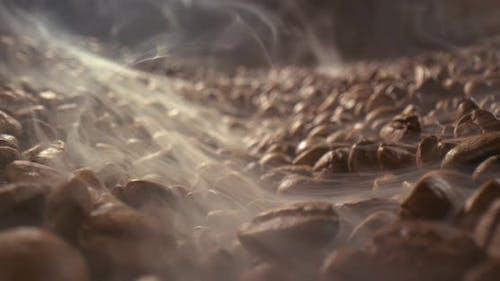 Nahaufnahme von Samen von Kaffee. Duftende Kaffeebohnen sind geröstet Rauch kommt aus Kaffeebohnen.