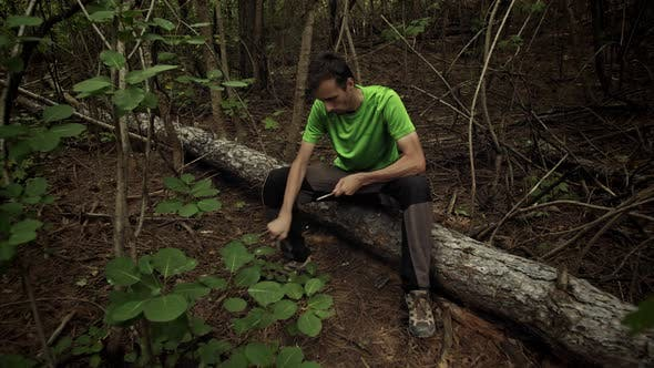 Survivalist in the Forest Sharpens a Stick with a Knife