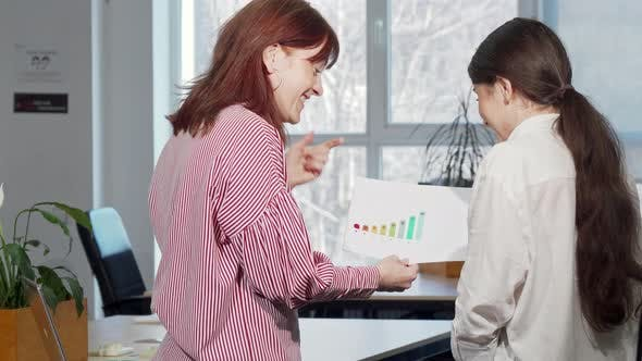 Cover Image for Rear View Shot of Two Female Colleagues Discussing Business Graphics