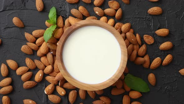 Thumbnail for Fresh Almond Milk in Wooden Bowl and Almonds on Black Stone Background