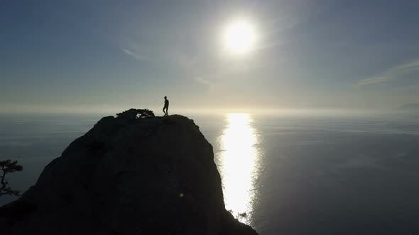 Thumbnail for Aerial Silhouette of Young Woman Walking on the Top of a Mountain Facing the Sea. Lady on the Summit