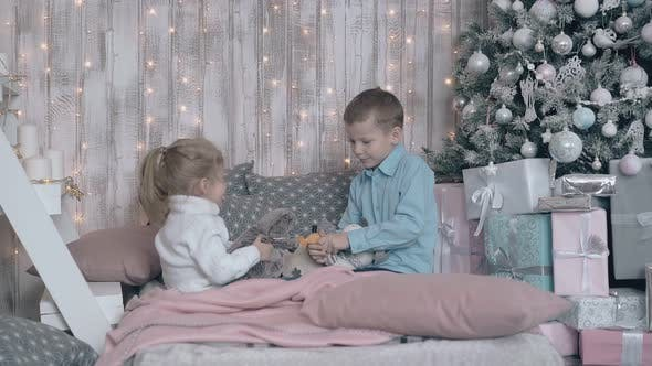 Small Brother and Sister Play with Toys on Pink Couch
