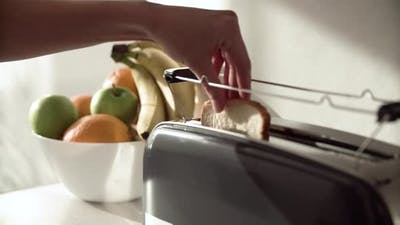 Breakfast. Woman Putting Slicing Bread In Toaster Closeup