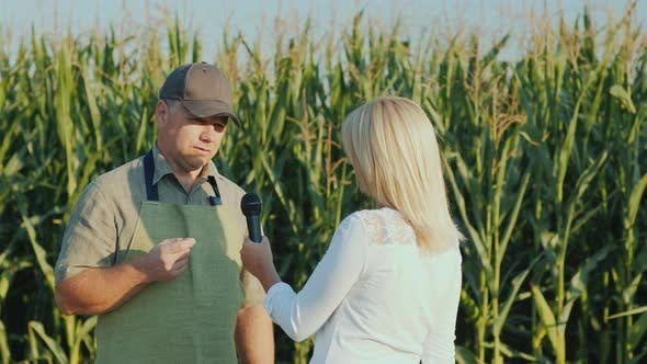 Thumbnail for A Journalist Interviews a Successful Farmer. Stand in the Background of a Field of Corn