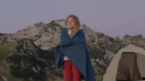 Travel Millennial woman with dreadlocks near the tent standing on top of hill looking at sunrise.