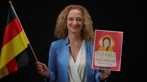 Smiling Confident Woman Holding German Flag and Planned Parenthood Funding Banner Looking at Camera
