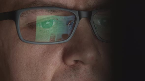 Thumbnail for Reflection Of Scrolling Sites In An Eyeglasses Of Young Adult Man Who Works On A Computer