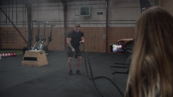 Buffed Male in Indoor Gym on the Battle Ropes with Girlfriend Taking a Video