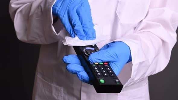 Thumbnail for a Doctor in Gloves and a Robe Handles a TV Remote. Disinfection From Viruses and Diseases. Epidemic