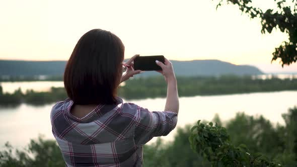 Thumbnail for A Young Woman Stands on a Hill Against the Background of the River and Mountains and Photographs the