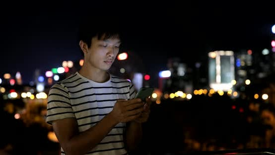 Thumbnail for Young man using mobile phone in city