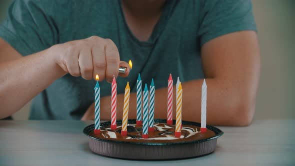 Man Is Lighting Candles on a Cake