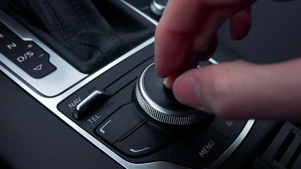 Thumbnail for A Man Turns and Presses a Knob on the Gearshift Box of a Luxurious Car - Closeup