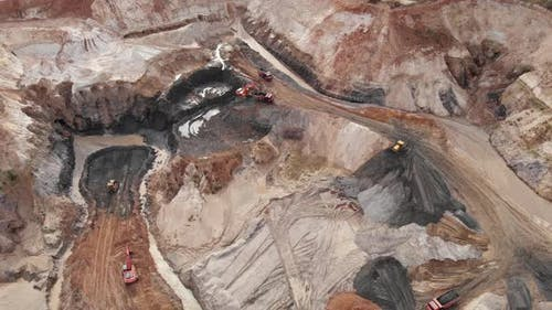 Aerial view of excavators and machinery are loading ore into dump truck in quarry.