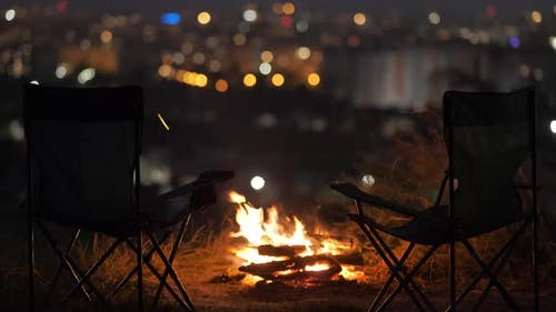 Two empty camping chairs near burning yellow camp fire at night.