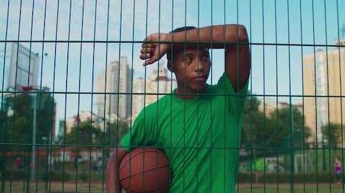 Athlet mit Basketball lehnte sich auf Sportzaun