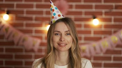 Portrait of a Birthday Woman with a Cap on Her Head