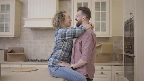 Bearded Man Stands Near Pretty Woman Sitting on Table in Big Half Empty Kitchen