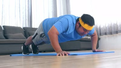 Plump Male Struggling To Do Push Ups At Home
