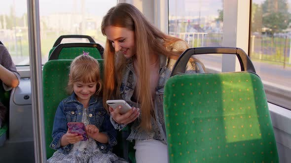 Child Girl with Mother Using Mobile Phone Internet Social Network Application While Traveling By Bus