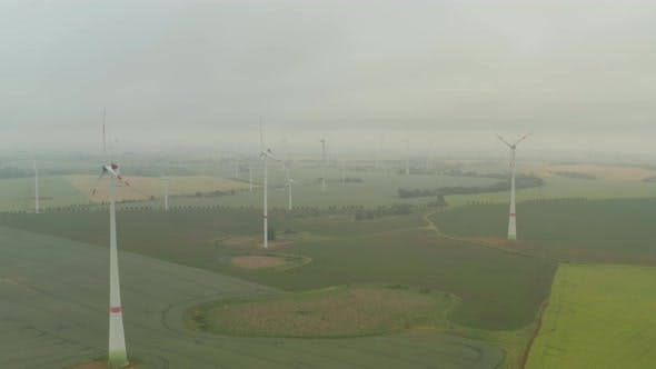 Thumbnail for AERIAL: View Over Foggy Agricultural Yellow Field with Multiple Wind Turbines Generating Power