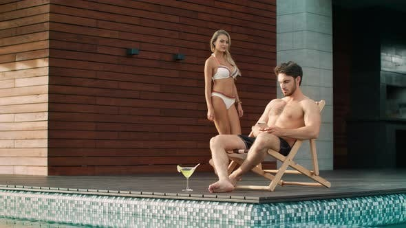 Thumbnail for Busy Man Sitting with Mobile Near Pool at Private Villa